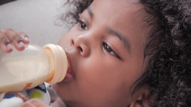 portrait of african american baby girl drinking from bottle on the bed in her room. life insurance, family, people, childhood and parenthood, portrait, lifestyle concept.video: diverse portraits - life insurance stock videos & royalty-free footage