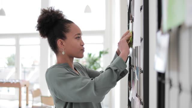 vidéos et rushes de portrait of african american businesswoman next to noticeboard - panneau d'information