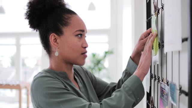 vídeos de stock, filmes e b-roll de portrait of african american businesswoman next to noticeboard - folheto publicação