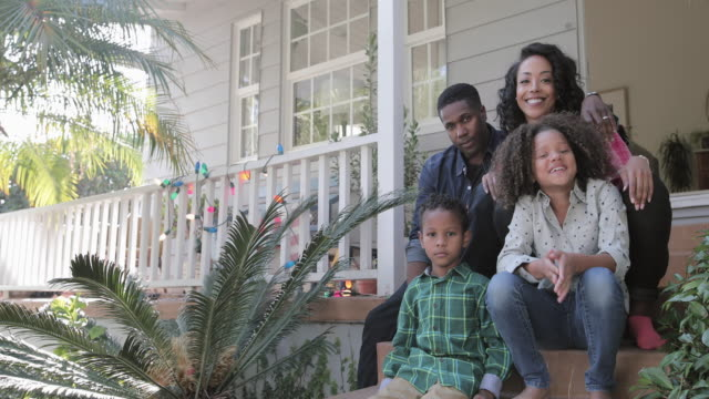 vidéos et rushes de portrait of african american family sitting outside home - latin american and hispanic ethnicity