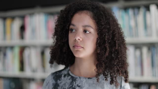 vidéos et rushes de portrait of african american high school student in library - élève du secondaire
