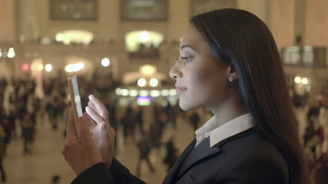portrait of african american women in business suit standing in public train station searching the web on tablet computer screen - abbigliamento da lavoro formale video stock e b–roll