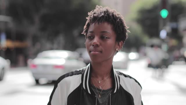 vídeos y material grabado en eventos de stock de portrait of african american young adult female on busy city street - igualdad