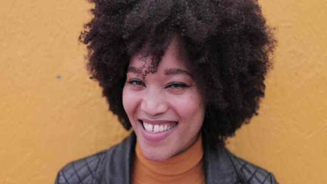 portrait of african american young adult leaning on bright yellow wall laughing - orange colour stock videos & royalty-free footage
