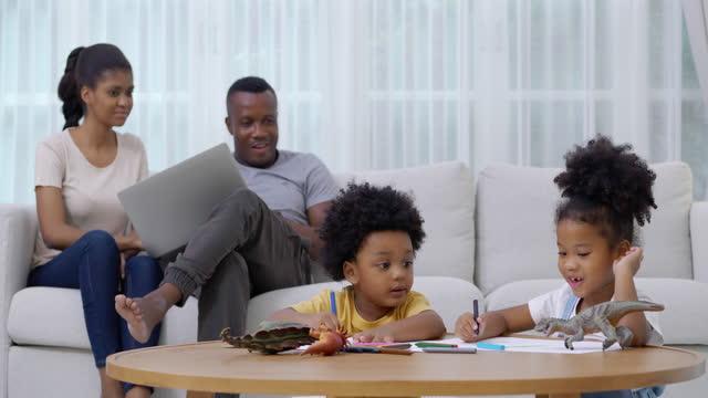 vídeos y material grabado en eventos de stock de retrato de niños africanos hermana y hermano de 2-3 años de edad de la educación en casa durante la noche durante para prevenir epidemias de coronavirus o covid-19 mientras padre y madre trabajan en casa en el sofá. concepto de las familias en sudáfri - new age