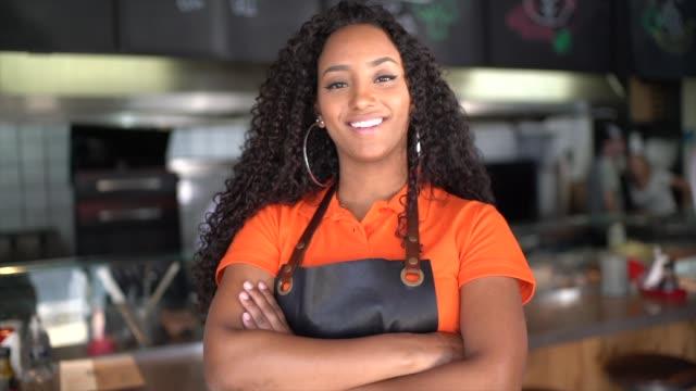 vídeos de stock, filmes e b-roll de retrato da empregada de mesa/proprietário africanos da etnia no restaurante - profissão na área de serviços