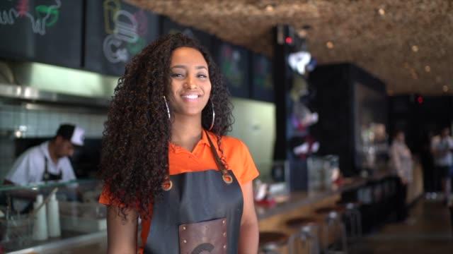 vídeos de stock, filmes e b-roll de retrato da empregada de mesa/proprietário africanos da etnia no restaurante - pequeno
