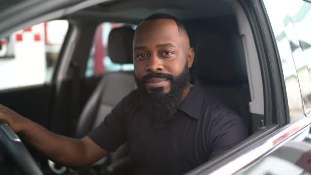vídeos de stock, filmes e b-roll de retrato do homem africano dentro de um carro - new