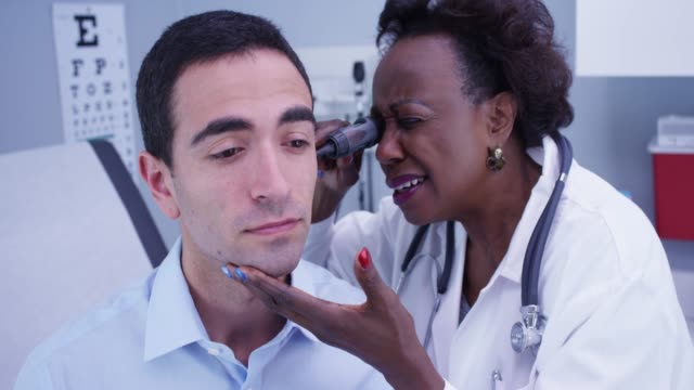 Portrait of African senior doctor using otoscope to inspect young patients ear