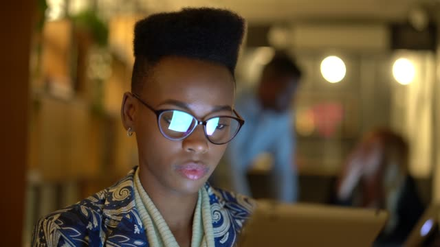 vídeos de stock e filmes b-roll de portrait of african young woman using tablet at night on coworking office - multi ethnic group