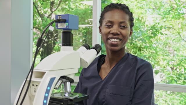vídeos de stock, filmes e b-roll de retrato do patologista fêmea africano-americano usando o microscópio no laboratório médico - cientista