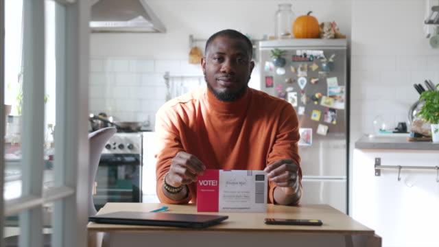 porträt eines afroamerikanischen mannes mit briefumschlag - wahlschein stock-videos und b-roll-filmmaterial