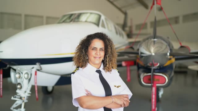 portrait of airplane pilot in a hangar and looking at camera - pilot stock videos & royalty-free footage