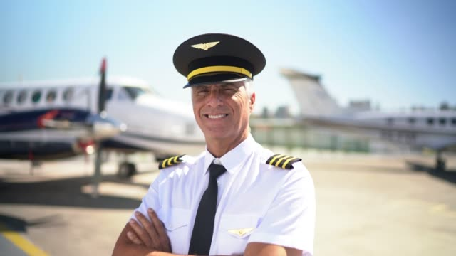 portrait of airplane pilot in front of a private jet and looking at camera - private jet stock videos & royalty-free footage