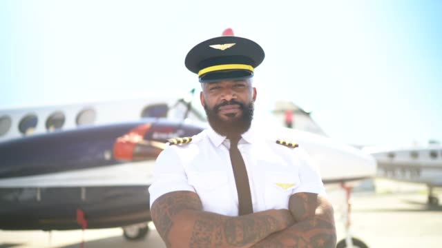 portrait of airplane pilot in front of a private jet and looking at camera - corporate jet stock videos & royalty-free footage