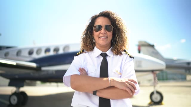 portrait of airplane pilot in front of a private jet and looking at camera - pilota video stock e b–roll