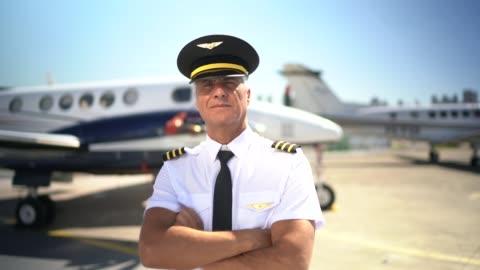 vidéos et rushes de verticale de pilote d'avion devant un jet privé et regardant l'appareil-photo - pilote