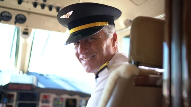 portrait of airplane pilot looking over shoulder in a private jet - captain stock videos and b-roll footage