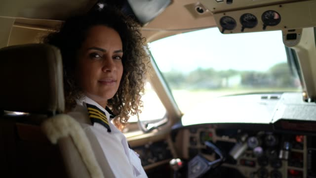 portrait of airplane pilot looking over shoulder in a private jet - captain stock videos & royalty-free footage