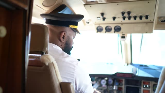 portrait of airplane pilot looking over shoulder in a private jet - aerospace industry stock videos & royalty-free footage