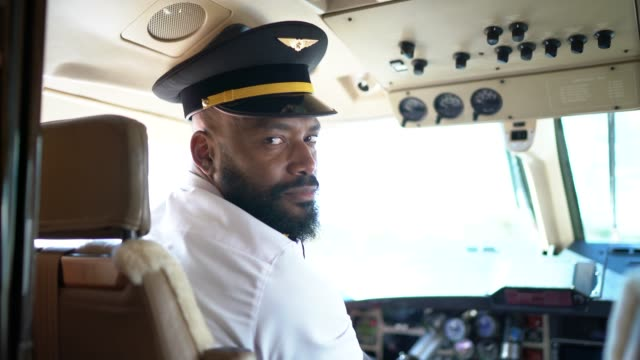 portrait of airplane pilot looking over shoulder in a private jet - pilota video stock e b–roll