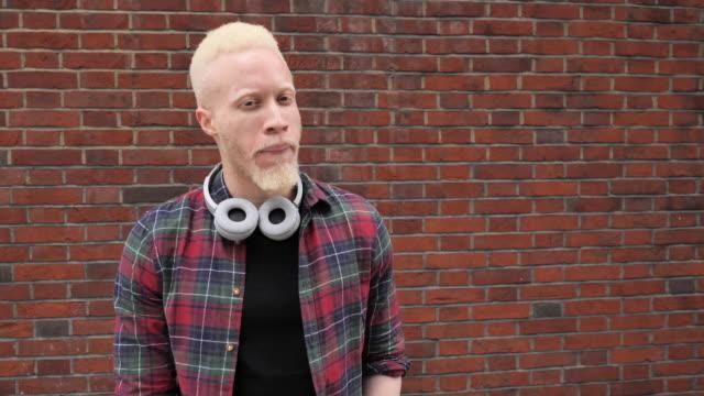 vídeos de stock, filmes e b-roll de retrato do indivíduo africano albino com auscultadores ao ar livre - juventude em reino unido - aço