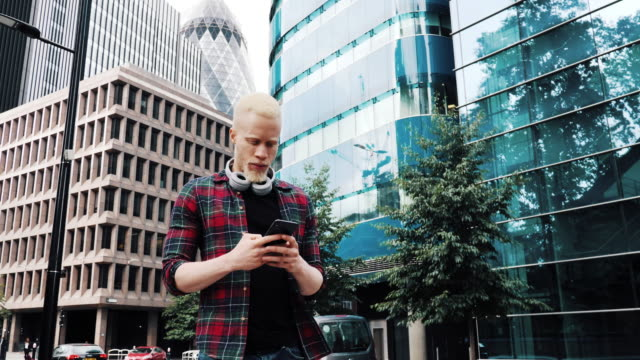 portrait of albino african guy with headphones using smart phone - youth in united kingdom - shirt stock videos & royalty-free footage