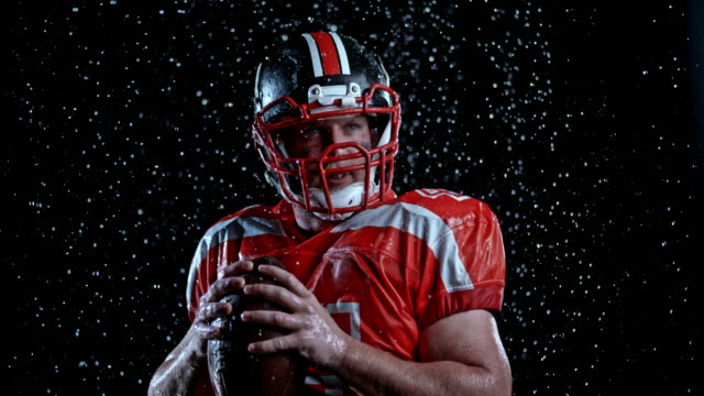 slo mo ld portrait of american football player holding the ball at night in heavy rain - american football ball stock videos & royalty-free footage