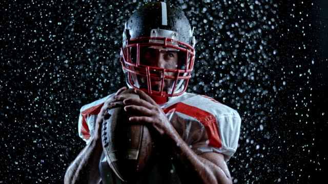 slo mo ld portrait of american football player in white jersey holding the ball at night in heavy rain - american football player stock videos & royalty-free footage