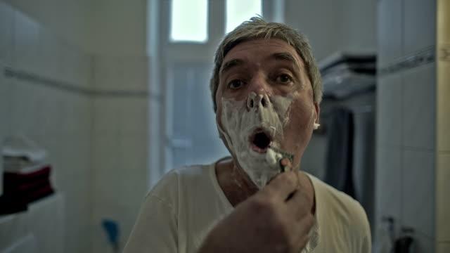 Portrait of an active senior man shaving his face