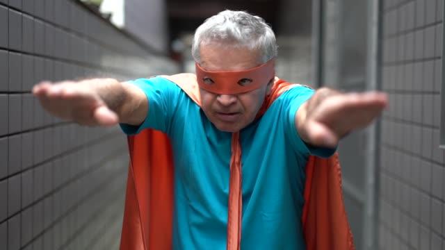 porträt von einem aktiven senior mann superhelden zu hause - mut stock-videos und b-roll-filmmaterial