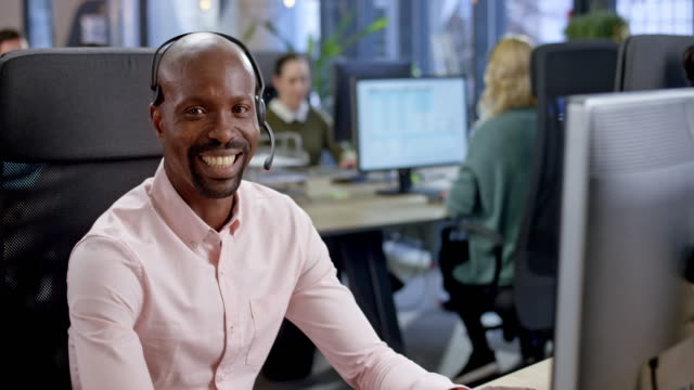 portrait of an african call center agent smiling while sitting at his desk - button down shirt stock videos & royalty-free footage