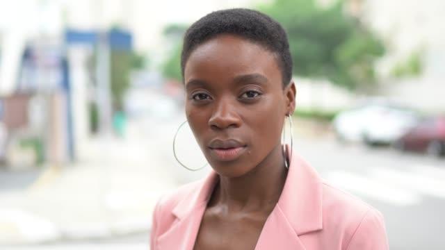 vídeos de stock, filmes e b-roll de retrato de uma mulher nova africana na cidade - coragem