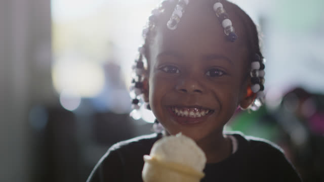 slo mo. cu. portrait of an african-american girl eating an ice cream cone with her brother at an ice cream shop - child stock videos & royalty-free footage