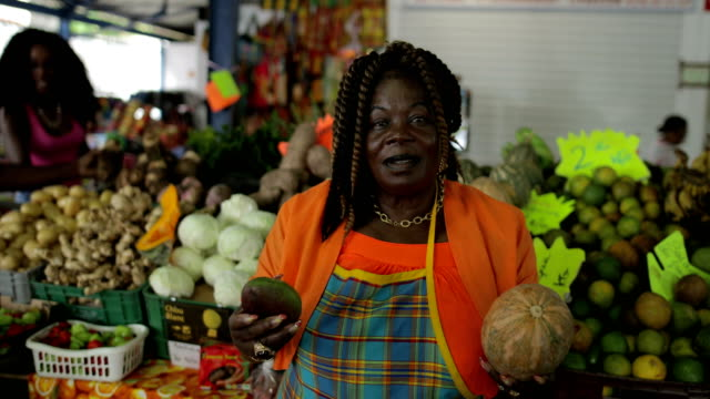 Portrait of an Afro-Caribbean market woman in front of her market stand in Martinique