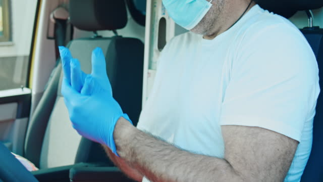 slo mo portrait of an ambulance driver putting on surgical gloves - glove stock videos & royalty-free footage