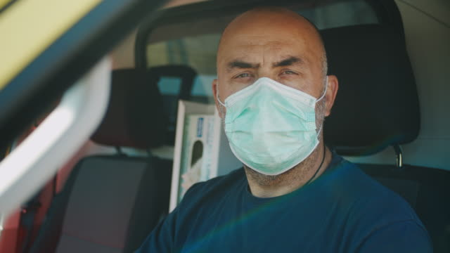 slo mo portrait of an ambulance driver wearing a mask - paramedic stock videos & royalty-free footage