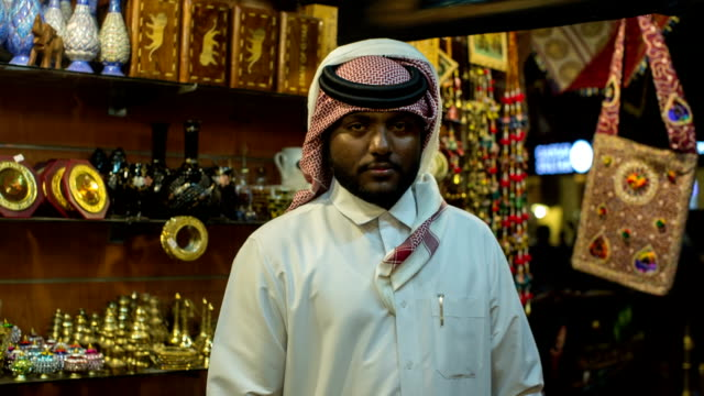 Portrait of an Arab businessman in his traditional costume in his gift shop in the Arab market in Doha, Qatar.