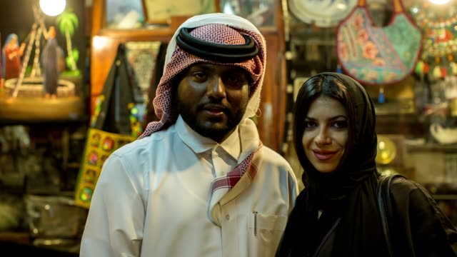 Portrait of an Arab businessman in his traditional costume with a woman in abaya in his gift shop at the Arabic market in Doha, Qatar