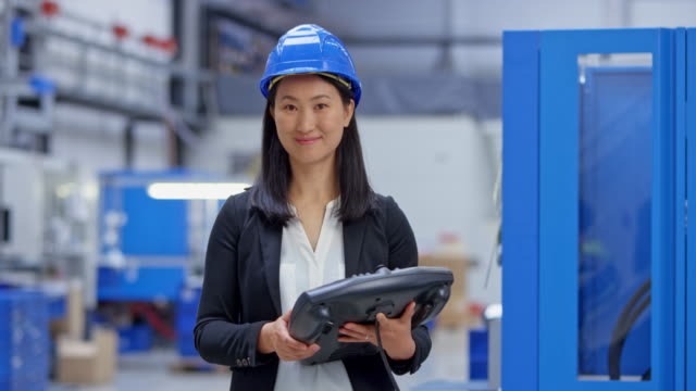 ds portrait of an asian female engineer holding the control panel for the machine in the background - health and safety stock videos & royalty-free footage