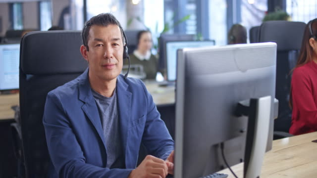 portrait of an asian male call center agent smiling into the camera at his workstation - waist up stock videos & royalty-free footage