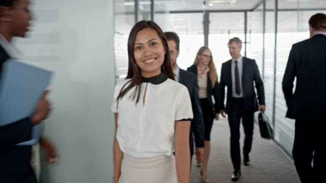 portrait of an asian office employee walking in the office hallway, ending the phone call and smiling into the camera - large group of people stock videos & royalty-free footage