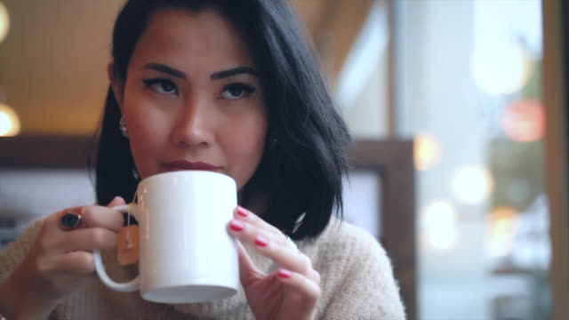 portrait of an asian woman sitting near the window and drinking tea at coffee shop - beautiful people stock videos & royalty-free footage