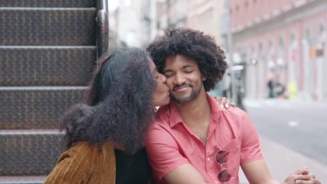 Portret van een aantrekkelijke Afrikaanse Amerikaanse echtpaar zoenen in de stad