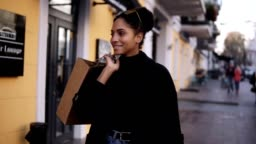 Portrait of an attractive mixed race girl smiling while walking down the street with little brown bag. Happy young woman walking after shopping by fancy streets city