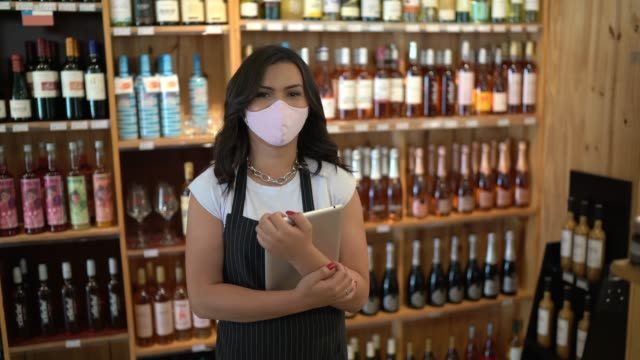 portrait of an employing using face mask holding a digital tablet in a wine store - selling stock videos & royalty-free footage