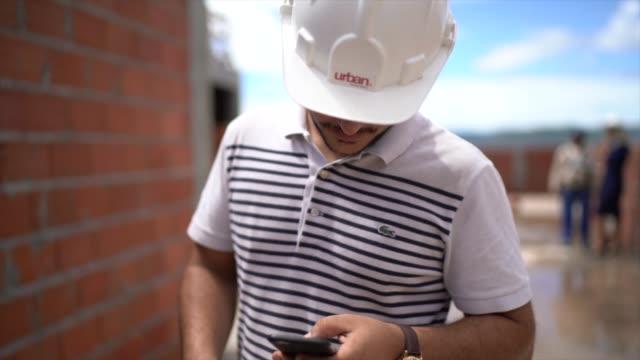 vidéos et rushes de portrait d'un ingénieur dans un chantier de construction utilisant le téléphone portable - architecte