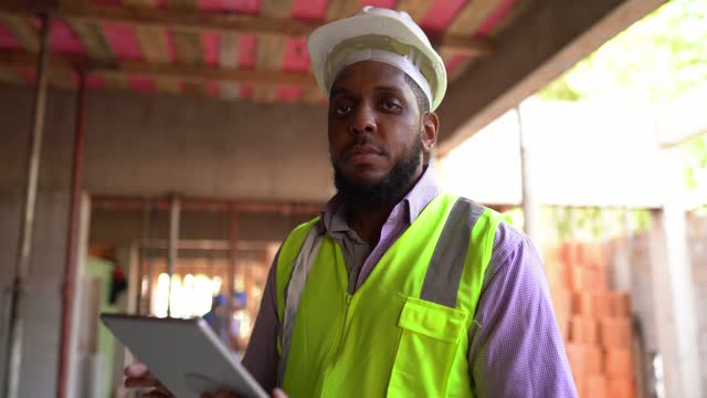 porträt eines ingenieurs, der mit einem digitalen tablet auf einer baustelle arbeitet - one mid adult man only stock-videos und b-roll-filmmaterial