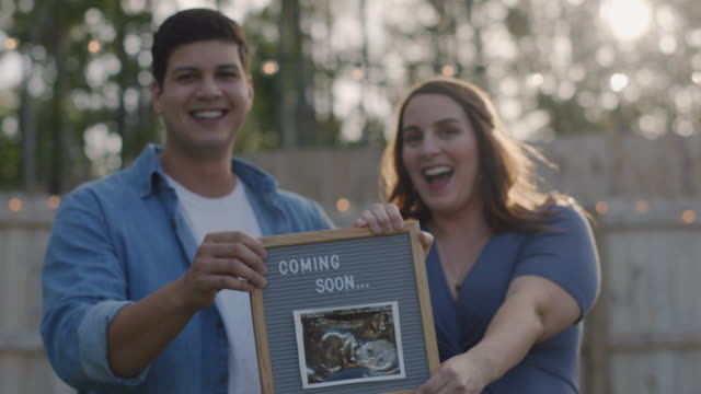 stockvideo's en b-roll-footage met slo mo. portrait of an expecting couple holding up a coming soon sign with an ultrasound photo - aankondigingsbericht