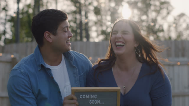 slo mo. portrait of an expecting couple holding up a coming soon sign with an ultrasound photo - creation stock videos & royalty-free footage
